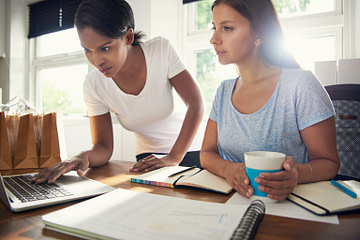 Two young female businesswomen doing research